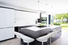 This modern kitchen features a island with a concealed extractor fan, alongside luxuries such as wine fridges, a double oven and Quooker boiling water tap. Kitchen Island Bench Designs, Contemporary Kitchen Island, Kitchen Design Open, Kitchen Island With Seating, Open Plan Kitchen, Kitchen Designs, Contemporary Interior Doors, Contemporary Decor, Layout Design