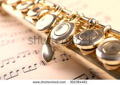 Silver flute on music notes background - stock photo