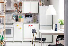 Køkken med hvide IKEA skabe, reol og spiseområde. De fleste ting er gjort personlige.