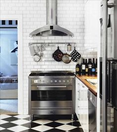 """Not exactly """"warm"""" but I like the black and white linoleum, wood counter, white tile, and nice stove and hood."""