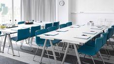 Конференц-зал с белыми столами и стульями, обтянутыми голубой кожей, с хромированными ножками