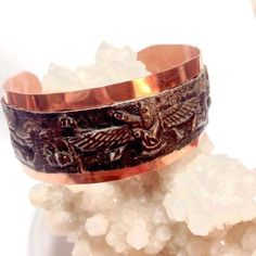 This bracelet is made with hammered copper and a strip of salvaged antique decorative metal which depicts an Annunaki. The decorative metal is estimated to be c.1910s. The Anunnaki a group of deities in ancient Mesopotamian cultures. The name means something to the effect of those of royal blood and has also been interpreted as those who came from heaven to earth. Whether angelic, demonic, alien or just a myth... thats up to your interpretation. This bracelet is a stunning one of a kind…