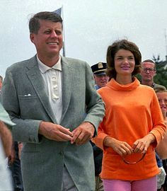 JFK and Jackie (in orange and pink!) stroll along a pier in Hyannis Port on July 19, 1960.