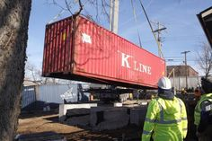 A shipping container was lowered by crane onto a foundation on York Street in Lexington Wednesday as part of the LuigART Makers project, which will provide live-work spaces that resemble the area's historic shotgun houses.