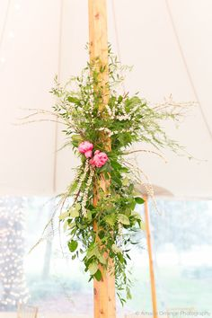 a grand sperry tent for the wedding reception with wood poles dressed with fern, vines, lemon leaf, spirea branches and coral charm peonies.