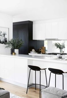 A mirror splashback amplifies natural light within this black and white monochrome kitchen. Modern Kitchen Renovation, Kitchen Interior, New Kitchen, Kitchen Remodel, Kitchen Design, Kitchen Decor, Kitchen Mirror Splashback, Kitchen Benchtops, Black Splashback