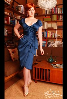 In blue (pictured) red and green. Old Hollywood glamour simply oozes from this satiny stunner.  Plunging neckline, faux wrap front, tulip skirt and back zipper. Better hire a bodyguard!