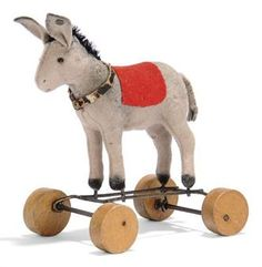 A STEIFF TINY DONKEY ON WHEELS, (1108ex), grey felt, bead eyes, black mohair mane, red cloth saddlecloth, leather collar, wire frame, wooden eccentric wheels and tiny FF button, circa 1920 --4¼in. (11cm.) high (some slight moth nibbling)