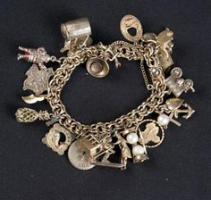 10K GOLD-FILLED CHARM BRACELET WITH APPROX. 20 CHARMS. SOME CHARMS ARE GOLD AND SOME ARE STERLING SILVER CHARMS