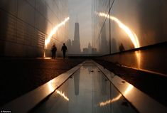 A man walks through the 9/11 Empty Sky memorial at sunrise across from New York's Lower Manhattan and One World Trade Center in Liberty Stat...