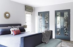 In the master bedroom, designer Christos Prevezanos mixed various shades of blue to give the room personality. The mohair-and-walnut bed was devised by Prevezanos, and the bench is a vintage Milo Baughman. The closet doors are painted in Down Pipe by Farrow & Ball and are inset with antiqued glass panels.