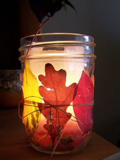 A small jar lined with wax paper, with about an inch of pebbles at the bottom.  On the outside, a few pretty leaves taped on, a bit of rafia, & some beads - pretty little tea light I made last November  :-)