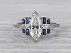 Vintage Art Deco engagement ring made in platinum and centered with a GIA certified 1.12 carat marquise cut diamond with H color and VS1 clarity. Accented with sapphires. Circa 1925 A striking and unu