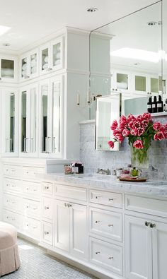 Designer Berkley Vallone's own bathroom. Lots of marble, mirrors and storage with cabinets up to the ceiling.