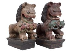 Description Two Chinese carved wood seated figures of Buddhist lions. Covered in polychrome pigments, each fierce beast with its forepaw resting upon a 'brocade' ball, on integral black stained rectangular bases.  Date 20th century.  www.collectorstrade.de