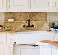 In this French country kitchen, designer Beverly Ellsley chose cedar limestone for the countertops and backsplash, which has a convenient shelf for soap.