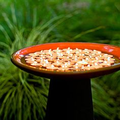 Float tea candles in a water-filled birdbath to create a mini firepit. On windy days, set tea lights in clear glass votive holders in a dry birdbath so they won't wobble.