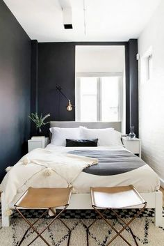 Small Swedish-inspired bedroom with black walls, simple bedding, and leather…