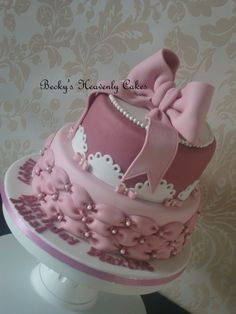 A celebration cake of pink shades.  tuffed pillows, cutout designs and a pink bow