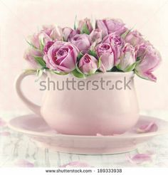 Bouquet of roses in a pink cup on wooden background with vintage textured editing by Anna-Mari West, via Shutterstock