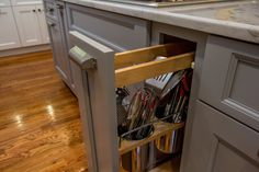 Gray island with kitchen utensils in pullout drawer and granite countertop