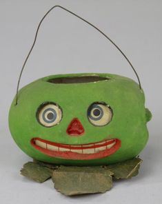 """Antique WATERMELON JACK-O-LANTERN CANDY CONTAINER  Germany, composition container done in colorful facial colors, green overall, paper insert for eyes and mouth, wire handle allows easy carry. 2 1/2""""."""
