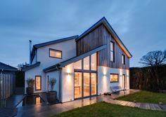 New build house with white render, timber cladding, vaulted slate roofs and full height glazing