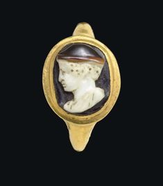 A ROMAN GOLD AND AGATE CAMEO FINGER RING   CIRCA LATE 1ST CENTURY B.C.   The thin plain hoop flat on the interior, rounded on the exterior, expanding to the two-tiered bezel, set with an oval stone in three layers, brown on white on black, sculpted with a bust of Mercury in profile to the left, the youthful god with curly hair, wearing a petasos and a mantle pinned to his shoulder