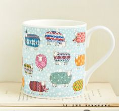 A colourful fine bone china mug featuring Mary Kilvert's Sheep in the Snow, wrapped in their finest woollen jumpers and scarves. Perfect for the festive season, this mug will cheer you through the winter months and beyond. Height: 8.5cm. Diameter: 7.5cm. Holds 9 fluid ounces of liquid. Dishwasher safe. Shipped in protective packaging.