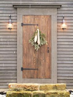 Don't care about the wreath, but love the door, lights and siding. The small picture looks likes the steps are bales of hay.. It would be perfect for a faux porch.