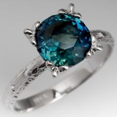 This spectacular 3 carat no heat blue green sapphire is set in a beautifully engraved vintage platinum mounting. The sapphire has a great cut that sparkles with distinct blues and greens. It is a very unique stone. We offer complimentary resizing to fit.