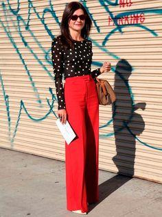 Mulher posa em frente à portão pichado vestindo pantalona vermelha e blusa preta de poá com bolsa vintage