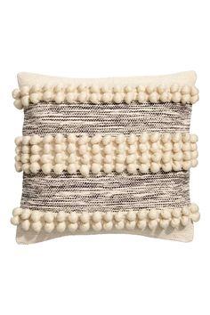 Een kussenhoes met een jacquardgeweven kwaliteit en decoratieve wollen bolletjes aan de voorkant en een achterkant van effen katoenen canvas. De hoes heeft