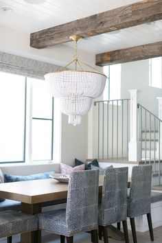 Lovely dining nook boasts rustic wood ceiling beams and a white beaded chandelier hanging . Wood Ceilings, Ceiling Beams, Dining Nook, Dining Room Design, White Chandelier, Ceiling Chandelier, Dining Lighting, Kitchen Lighting, Wood Beams