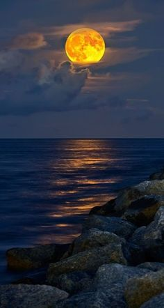 Moon over water, just off the rocky shore.