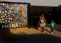 A girl and boy walk past a hand-painted mural in honour of the former president Nelson Mandela. The township's major connection to fame dates back to 1943 when Mandela stayed for a short time while studying at the University of South Africa. Credit: Kim Ludbrook/EPA