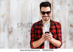Always in touch. Handsome young man holding mobile phone and smiling while standing against the wooden wall