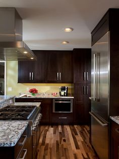 To add contrast to the dark contemporary wood cabinets, beautiful hardwood floors with various shades of brown are used throughout the kitchen. The warmer slats of wood tie in well with the soft yellow walls.