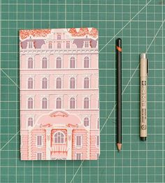 Carry the grandeur and beauty of The Grand Budapest Hotel with you in the form of this whimsical notebook. The ornate façade of the hotel graces the cover of the notebook, printed in pink, purple and red, to capture all of the fine details. Inside the pages are blank, to fill with your travel plans, sketches and dreams.