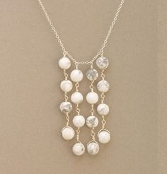 Fun dangle necklace, maybe with pearls and an accent color.