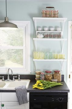 Hang bracketed shelves in a tight space — they'll keep you organized without the bulk of cabinets, and are the perfect place to display cute glassware. They're perfect for a functional storage space in a kitchen, or a more aesthetic arrangement in the living room. Click through more quick decorating ideas for your home.