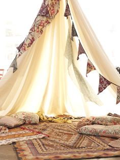 Similar set-up to what I have in mind. Teepee with draped banners, with quilts…