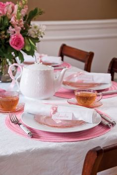 A white tablecloth graced with bright pink place mats, white china, and vintage depression glass creates a lovely tablescape for a Pink Tea.