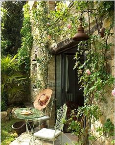 Wonderful cave-like doorway gives a natural landscape cozy look to this small home's patio area.