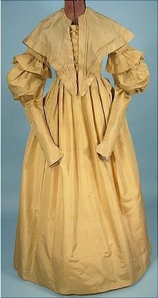 """c. late 1830's Dress of Golden Silk with Matching Pelerine! Like going back in time... this dress is in superb, strong condition (other than dark underarm stains which are hardly seen when displayed and slight old repairs underarm). Any other issues are so minor, they are hardly worth a mention. This dress has it all!  Pleating, ruffles, stitched down gigot sleeves, tight lower sleeves, ""v"" at waistline at front, cording, ""corset"" like detailing at front bodice."""