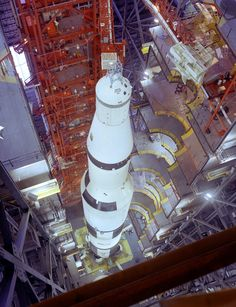 AS-501. Apollo 4 Saturn 5 rocket in the VAB high bay. Still has the black upper roll pattern (like AS-500F) on the S-1C intertank skirt, which will be painted over in white before flight. The tops of the engine fin fairings haven't yet been put on and the CM seems to be getting lowered to top off the stack!