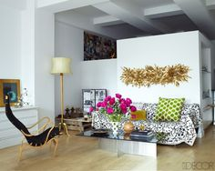 12 White Rooms with Pops of Color: Funkier than the usual Elle Decor interiors, this loft space has an eclectic mix of mid-century, contemporary, and boho pieces. The main elements are black, white, and wood. It's the green ikat pillow and hot pink flowers that add color. And the brass wall sculpture adds shine.