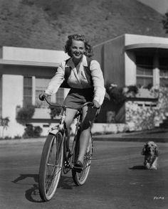1940's actress and pin-up girl, Elyse Knox, riding a bike and being followed by a cocker spaniel puppy.