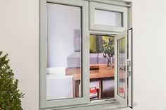 An open uPVC Casement window with a chrome handle, in an Olive Grey colour