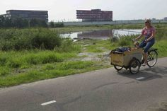 A woman bicycles past land that was meant to used for a big housing project in Lansingerland August 14, 2012. The euro zone crisis is washing over